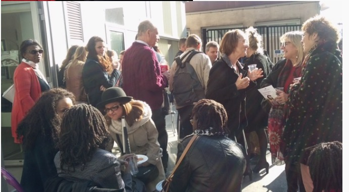 groupe de personne devant le local de l'association (certains ont un verre à la main)